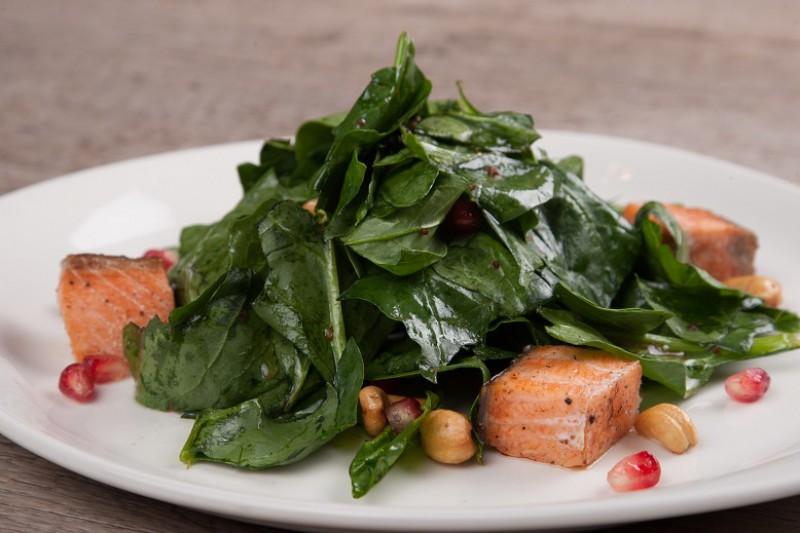 Запеченный лосось с листьями свежего шпината, орешками кешью и зернами граната